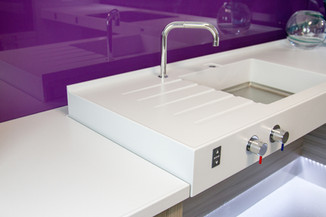 State-of-the-art wheelchair accessible sink designed by Adam Thomas, in solid surface material, with front mounted tap controls and flexible tap.