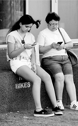 This black and white image shows a mother and daughter using their phones to connect to someone.