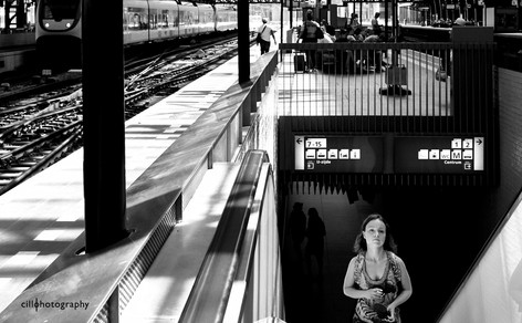 Project Normalness by documentary photographer Cilla Rijnbeek: a young woman in a flower dress walking up the stairs to reach the train platform of Amsterdam CS.