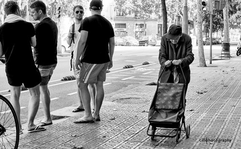 Project Normalness by Documentary Photographer Cilla Rijnbeek: young men having fun and an old man pushing a heavy load in Barcelona.