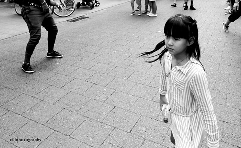 Project Normalness by documentary photographer Cilla Rijnbeek: an Asian looking girl watching the street acrobats in the shopping street of Antwerpen, The Meir.