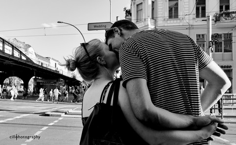 Project Normalness by documentary photographer Cilla Rijnbeek: a couple kissing in front of a traffic sign with the phrase Wedding on it, a borough in Berlin.