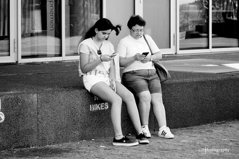Project Normalness by documentary photographer Cilla Rijnbeek: mother and daughter sitting next to each other, both looking at their phones.