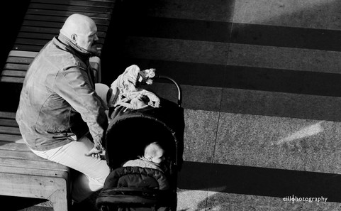 Project Normalness by documentary photographer Cilla Rijnbeek: a bold father and his bold baby boy both looking up with the same posture at the indoor Arena Mall in Den Bosch.