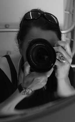 This Black and White image shows Documentary Photographer Cilla Rijnbeek taking a selfportrait with her camera in a convex mirror.
