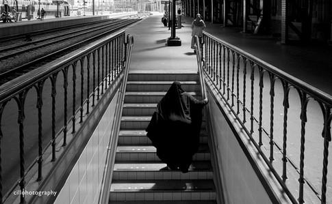 Project Normalness by documentary photographer Cilla Rijnbeek: a woman wearing a niqab coming up the stairs in beautiful light at a platform of Amsterdam CS.