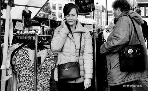 Project Normalness by documentary photographer Cilla Rijnbeek: a funny older woman who is on the phone while shopping at the market for cloths in Den Bosch.