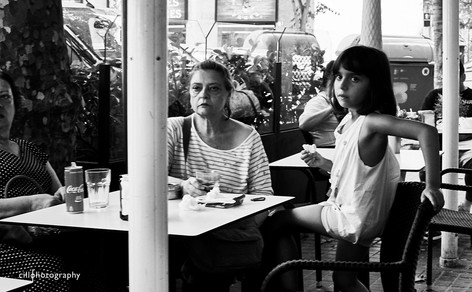 Project Normalness by documentary photographer Cilla Rijnbeek: an older woman with folds, ridges in her face that shows a life lived and a young beautiful little girl at a cafe in Barcelona.