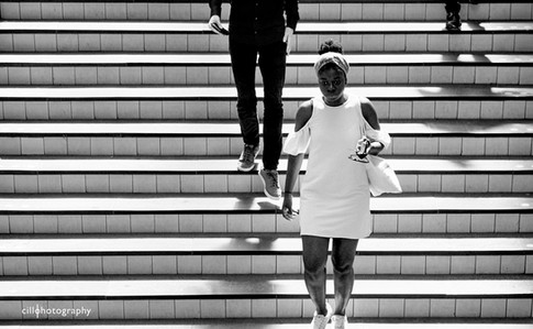 Project Normalness by documentary photographer Cilla Rijnbeek: beautiful woman in a white dress coming down a striped stairway into the underground metro of Amsterdam Amstel.
