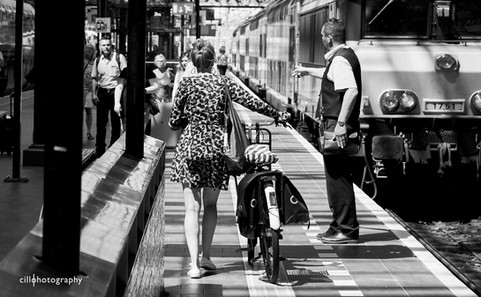 Project Normalness by documentary photographer Cilla Rijnbeek: a woman in a leopard print dress walking on a train platform with her bicycle past the train guard.