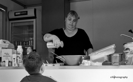 Project Normalness by documentary photographer Cilla Rijnbeek:  a fries entrepeneur salting a boy's fries in a mobile snack bar in Rotterdam.