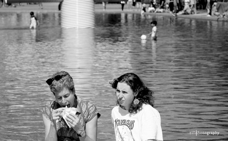 Project Normalness by documentary photographer Cilla Rijnbeek: a woman who is eating a sandwich in a funny way sitting at the Museumplein in Amsterdam.