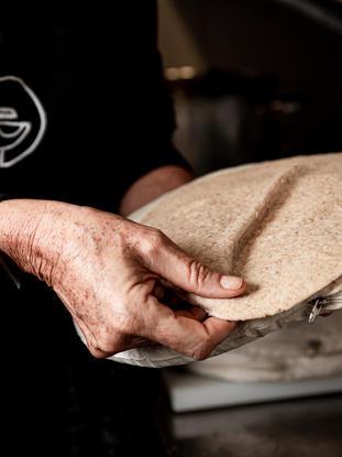 Esto este es un paso en el proceso de cocinar el Saj. Hay que colocarlo en un cojín al que llamamos 'Qara'. Luego la pegamos en la parrilla ardiente en forma de cúpula caliente, y luego aparecen las burbujas. La pelamos del Saj para empezar a enrollar tu Manoushe.