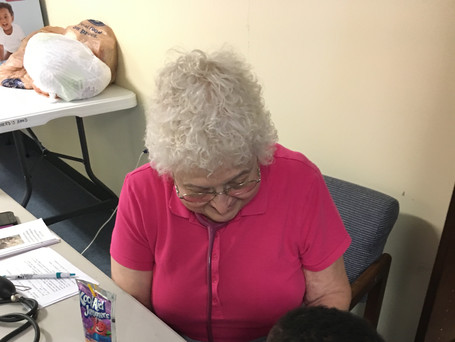 Volunteer nurse Jean lets a young visitor listen to his heartbeat.