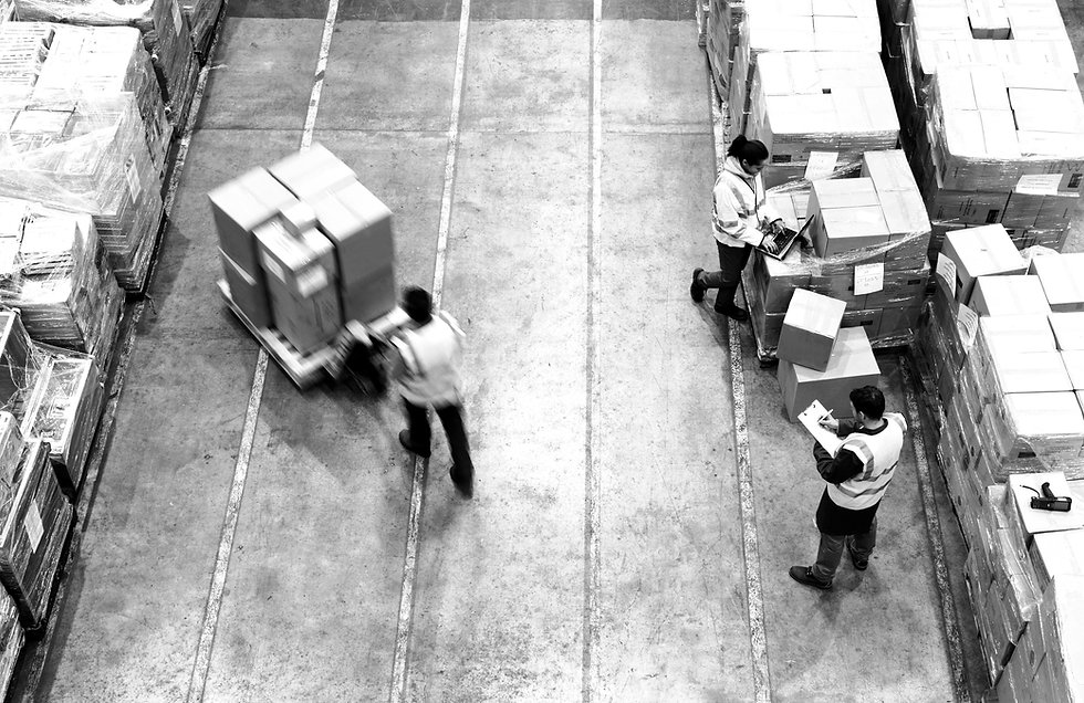 View down on a shipping dock. stacks of boxes. A worker moving a pallet of boxes. Two other workers.