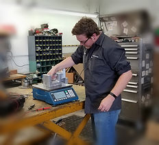 A calibration technician putting weight on a scale.