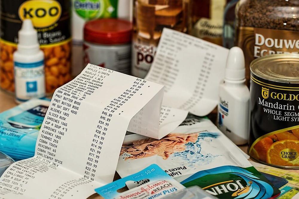 scontrino fiscale con decine di prodotti comprati attorno