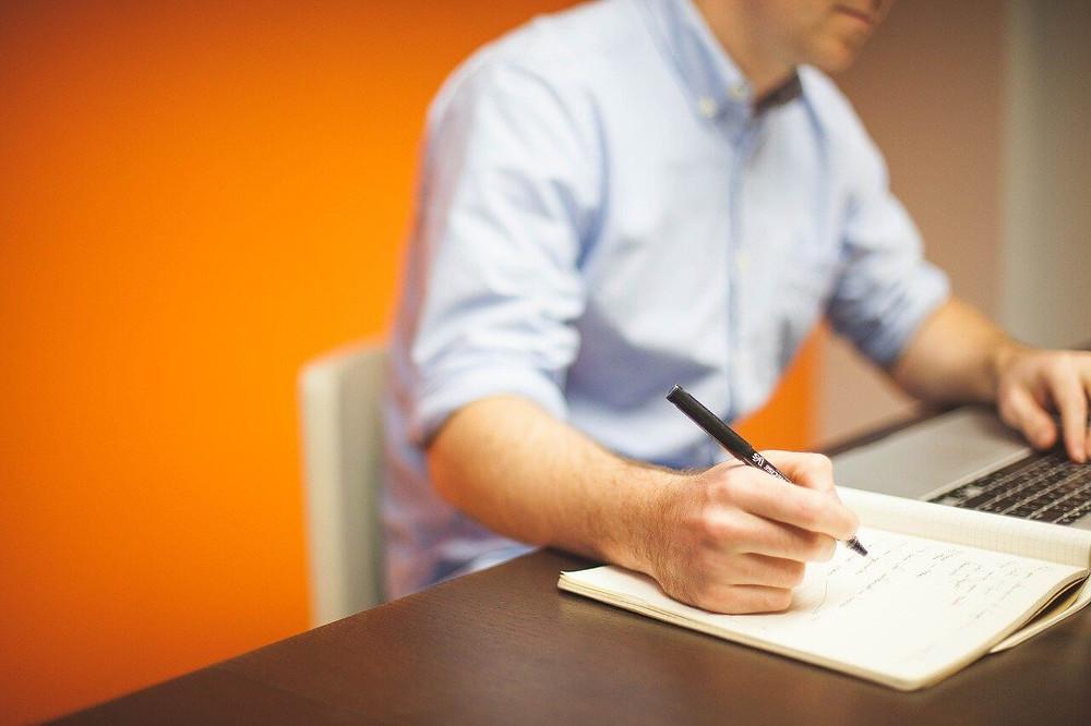 ragazzo che scrive in un'agenda mentre lavora al pc