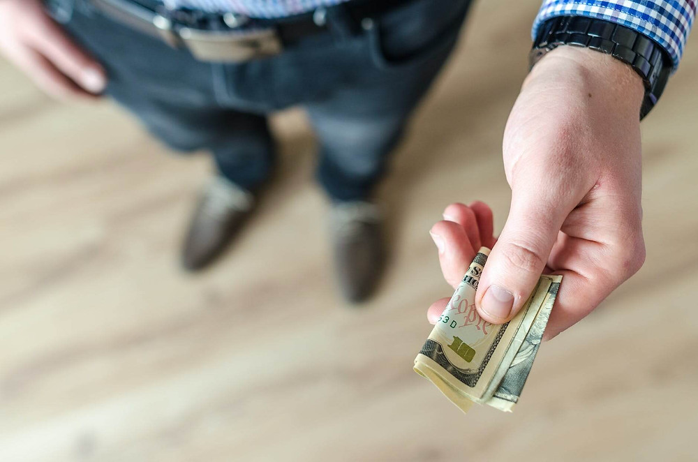 persona che tiene soldi nella mano