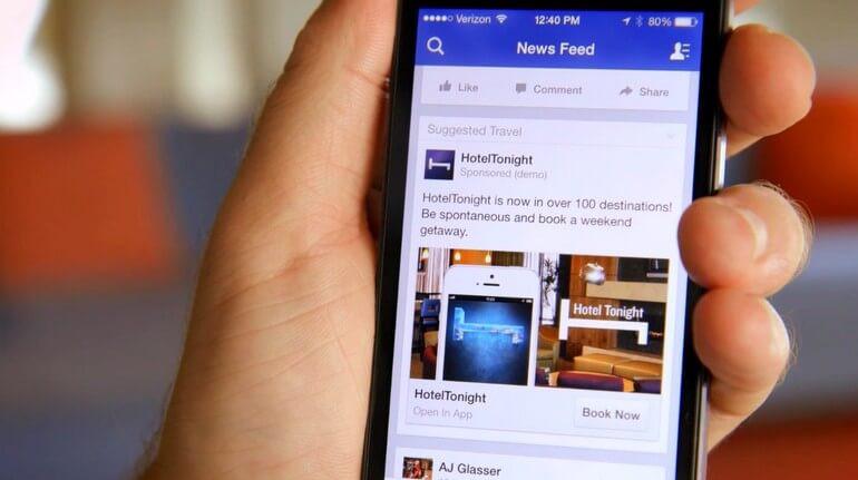 smartphone tenuto in mano che mostra un'inserzione sponsorizzata su facebook