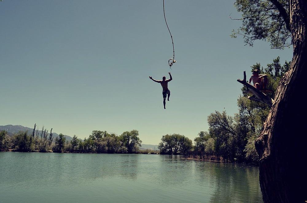 uomo felice che salta da una corda per tuffarsi in un lago