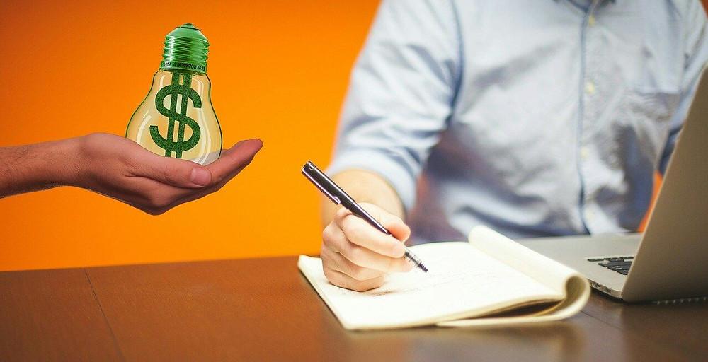 scrivere un testo con una mano che tiene una lampadina con il disegno del dollaro