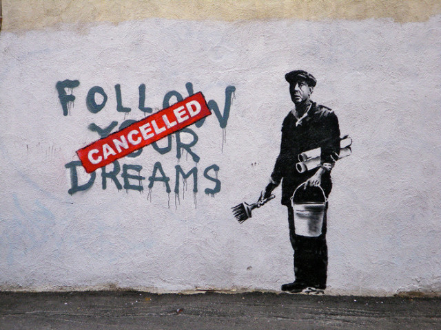 """A graffiti art by Banksy where a guy has painted """"Follow your dreams"""", but on top of the text, as if stamped, it says """"CANCELLED"""" in red"""