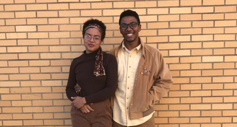 R-L: Kevin Leaven and Grace Carter wearing brown standing against a brick wall, posing, smiling