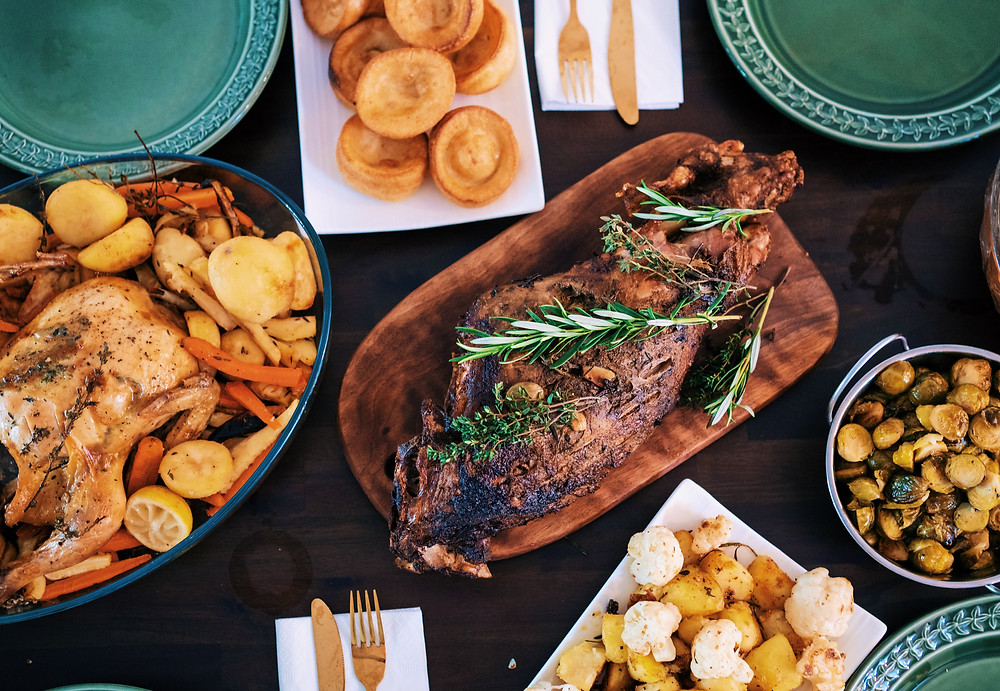 A flat lay of couple of dishes: Lamb leg at the center, another meat dish to the side, and two other side dishes on the top and bottom all set on a wooden table. This photo was sourced from Unsplash.com and was taken by Rumman Amin