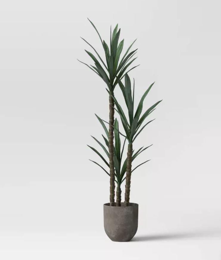 faux Dracaena plant in gray cement concrete planter