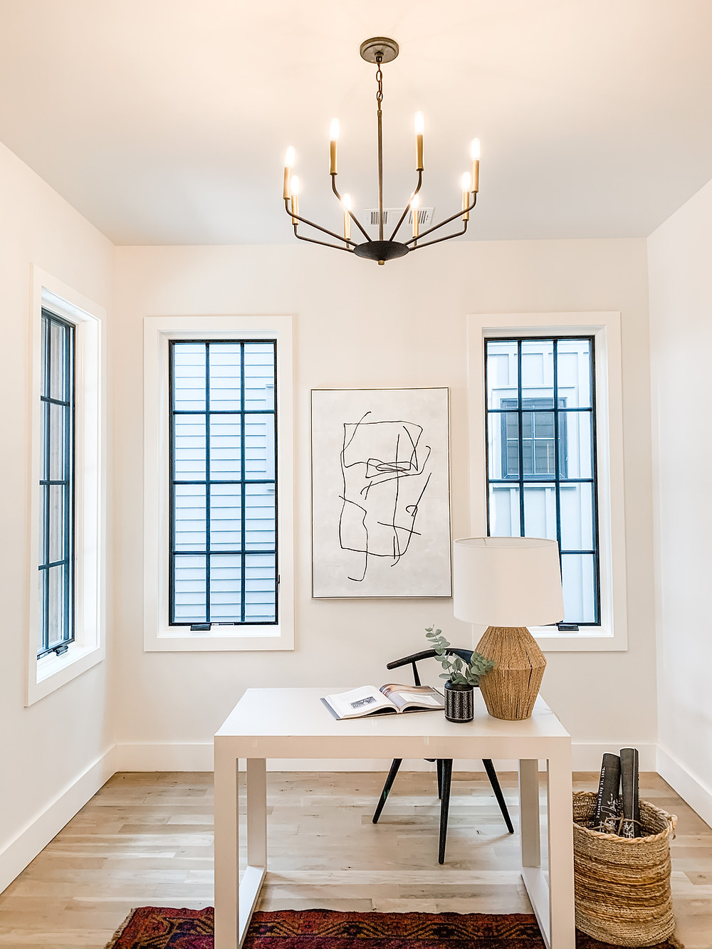 white home office work from home space study white desk black windows office chandelier