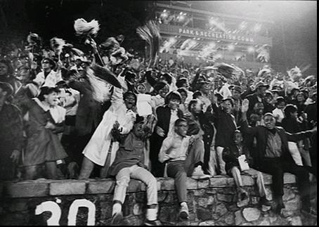 The crowd cheers at the 1976 Queens City Classic at Memorial Stadium.