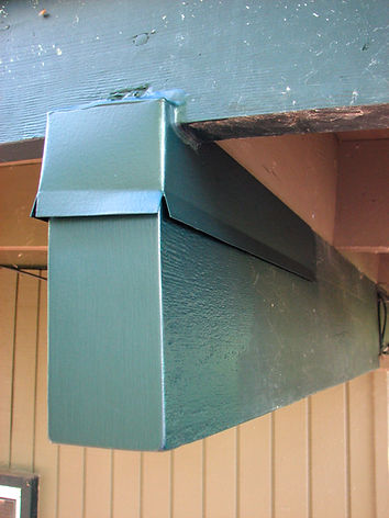 "A custom-fabricated beam cap installed on a roof beam. To be effective, even in wind driven rain, the ""joint"" at the fascia is sealed with an elastomeric sealant."
