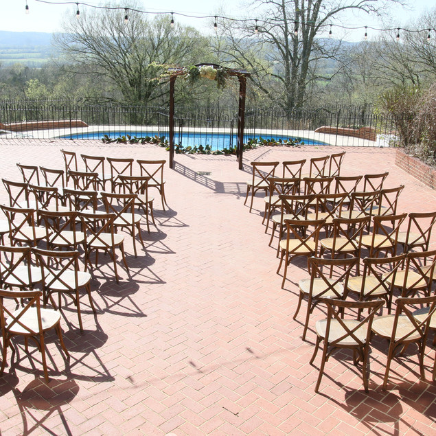 The Veranda, adjacent to the 10,000 square foot estate, provides the perfect mountaintop backdrop overlooking rolling hills, boasting stunning vista views. This versatile option can be customized for a reception, dance floor, or sunset ceremony.