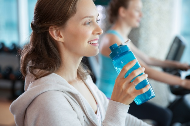 woman-smiling-with-a-bottle-of-water_1262-704