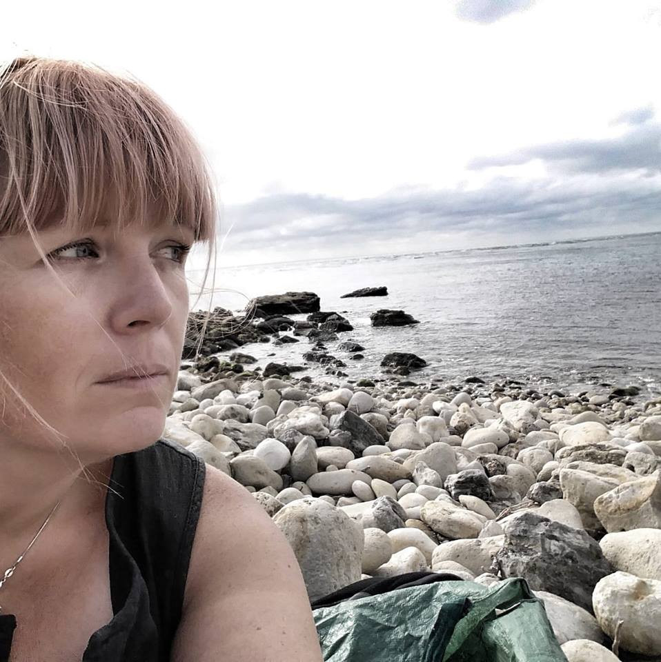 Lucy Bell looks out over stoney beach towards sea