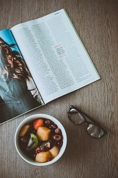 eyeglasses-beside-bowl-of-food-and-magaz