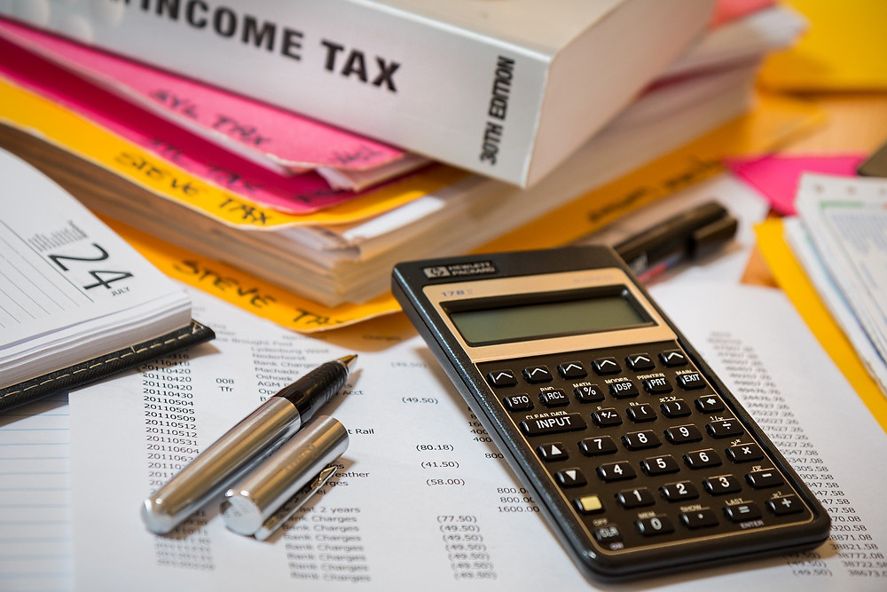calculator, pen and financial documents