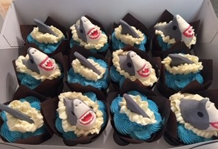 ASSORTED CUPCAKES WITH SHARK THEMED CUPC