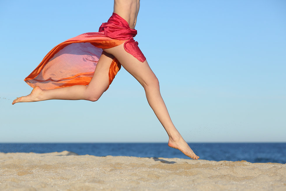 Woman legs jumping on the beach happy wi