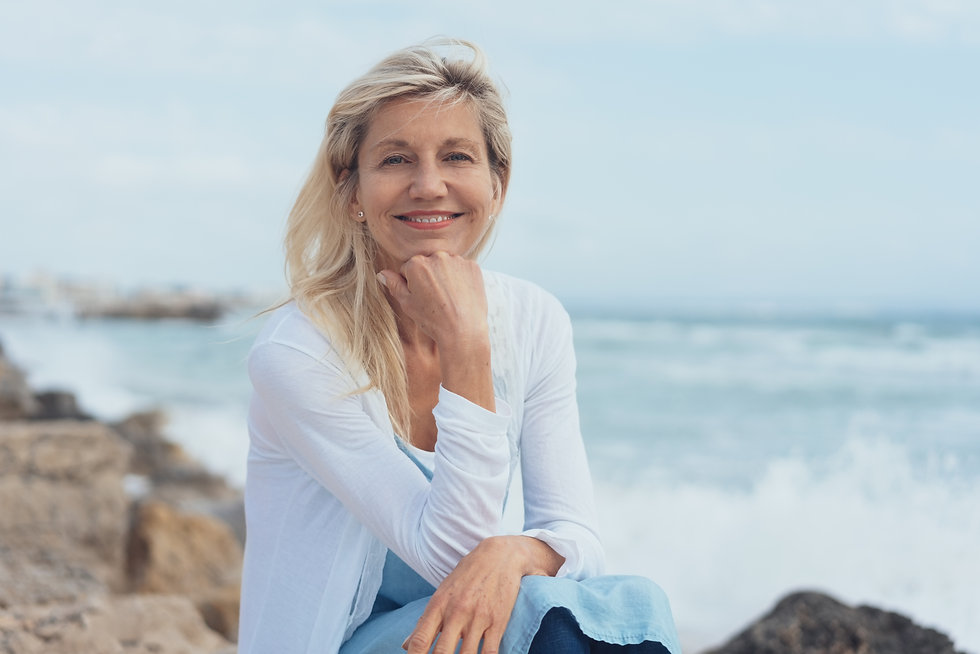 Smiling friendly woman relaxing on rocks
