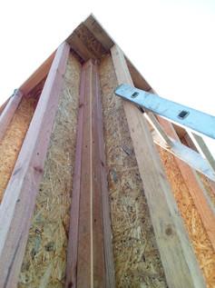 Угол дома снаружи пока выглядит так. Потом будет прибит ещё один элемент, формирующий внешнюю грань стены. Виден конструктивный брусок 50х50, содиняющий стойки двух стен в единый жёсткий угол.