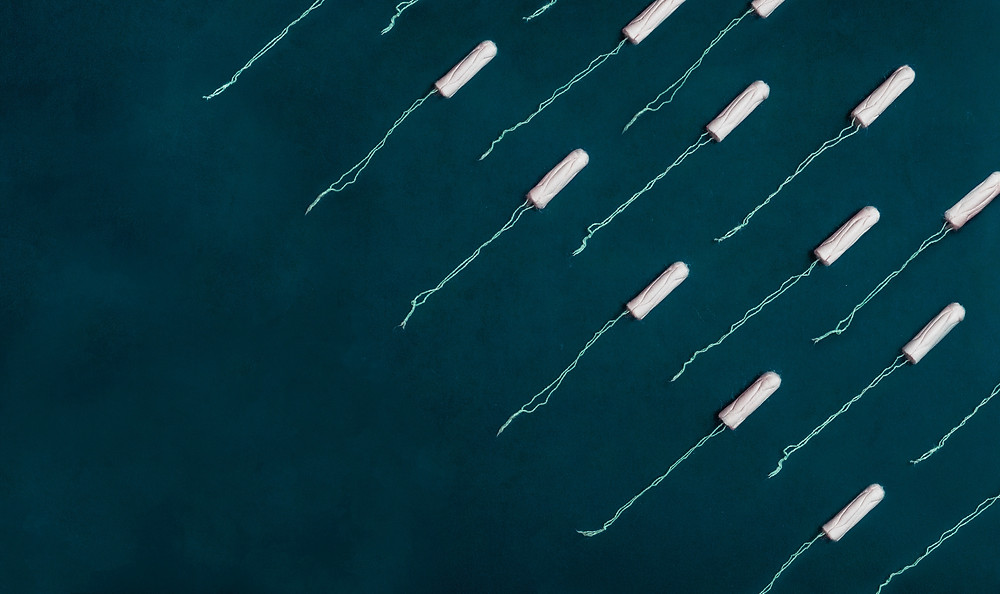 A series of white tampons on a blue backdrop.