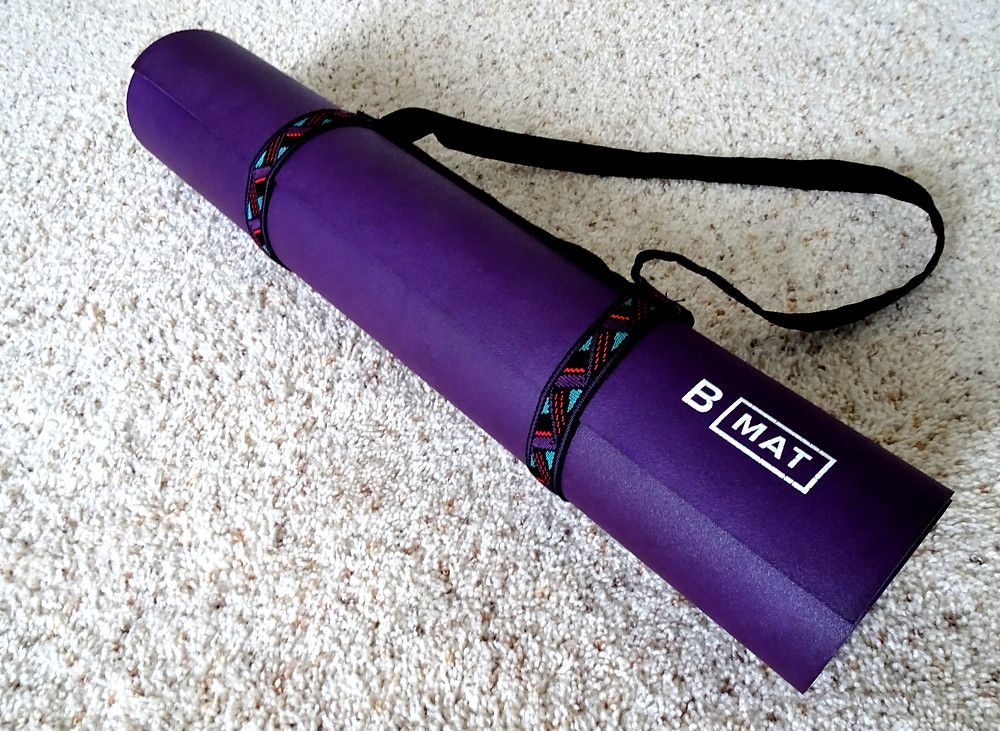 Rolled purple yoga mat with a tribal-printed carrying strap.