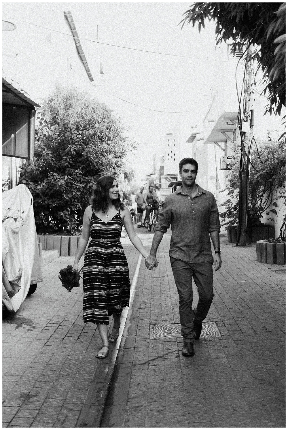 Black and white image of couple strolling in Tel Aviv