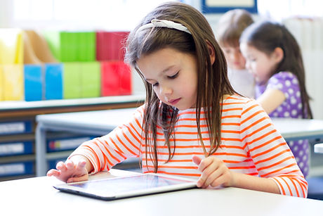 Young girl looking at tablet in classroom