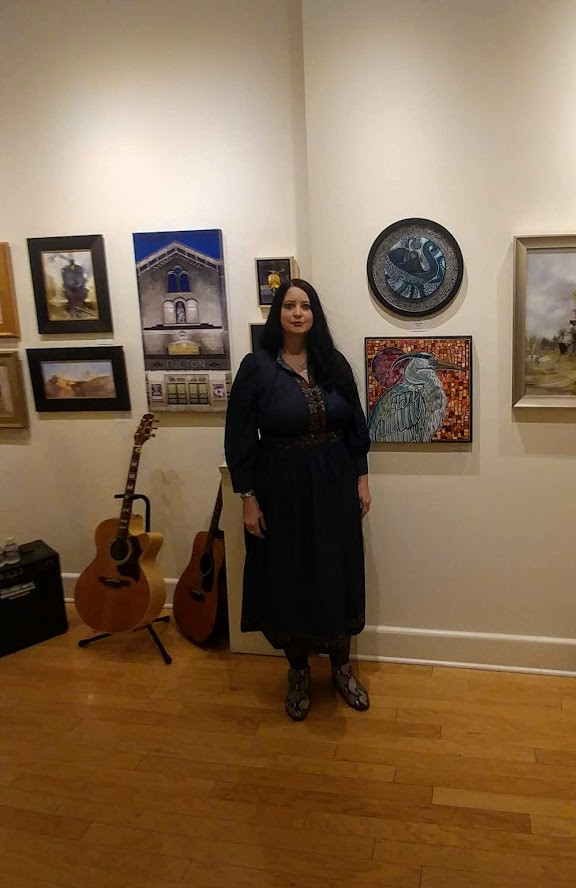 Artist Lynnette Shelley with two of her works at Red Raven Art Company, Lancaster, PA