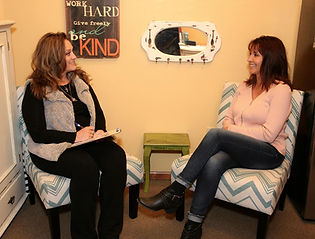 Light Therapist Lisa Chadsey sitting down with a client for a consultation