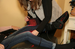 Light Therapist Lisa Chadsey applying a light system to a client's leg