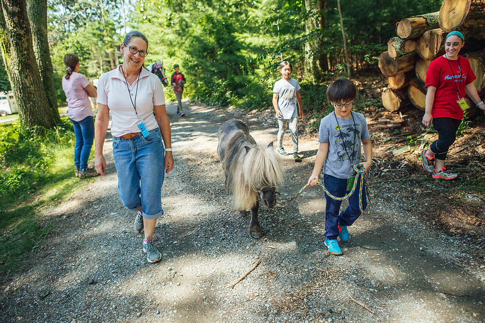 Volunteers and kids walking and smiling together on a trail with a pony